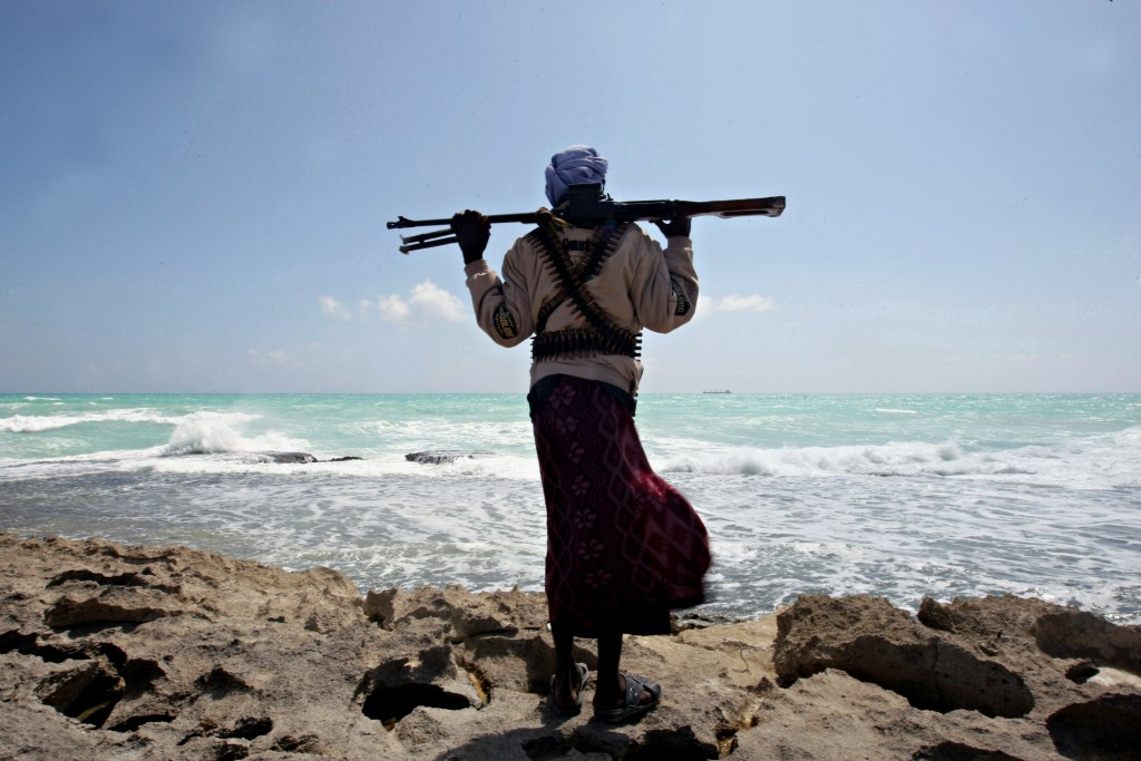 "(FILES) -- A file photo taken on January 7, 2010 shows an armed Somali pirate along the coastline while the Greek cargo ship, MV Filitsa, is seen anchored just off the shores of Hobyo, northeastern Somalia, where its being held by pirates. On the 20th anniversary of president Mohamed Siad Barre's ouster that triggered Somalia's descent into chaos and one of Africa's longest civil wars, prospects for peace remain slim, analysts said. The Horn of Africa country is now best known to the outside world for being the place that inspired the Hollywood war movie ""Black Hawk Down"" and the reason the term ""failed state"" was coined. AFP PHOTO / MOHAMED DAHIR (Photo credit should read MOHAMED DAHIR/AFP/Getty Images)"