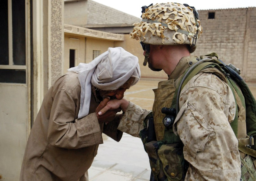 An Iraqi civilian kisses the hand of U.S. Marine Cpl. Joseph Sharp from Peoria, Ill., after Marines from the 1st Battalion 5th Marines gave him a supply of food and water in Fallujah, Iraq, Monday, April 19, 2004. (AP Photo/John Moore)