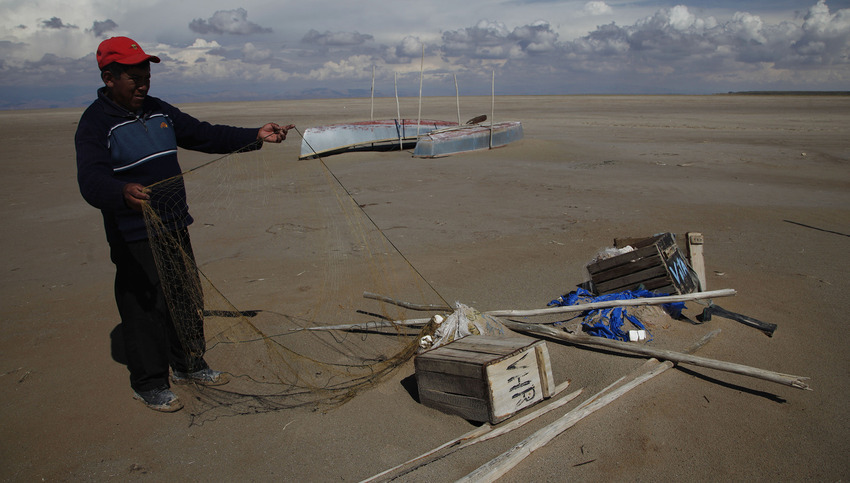 In this Jan. 12, 2016 photo, Abraham Fulguera checks his abandoned fishing net in Lake Poopo, on the outskirts of Untavi, Bolivia. Poopo is now down to 2 percent of what was normal, regional Gov. Victor Hugo Vasquez calculates. Its maximum depth once reached 16 feet. (AP Photo/Juan Karita)