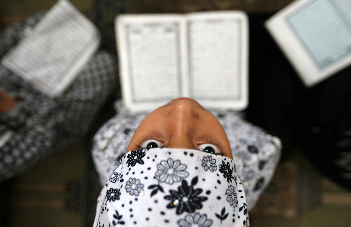 A Palestinian girl reads the Koran during the holy fasting month of Ramadan at a mosque in Rafah in the southern Gaza Strip June 8, 2016. REUTERS/Ibraheem Abu Mustafa - RTSGIXG